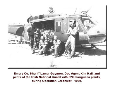 Law enforcement next to helicopter with load of confiscated marijuana