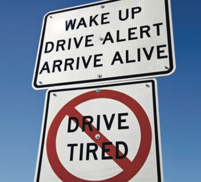 "Signs reading ""wake up drive alert arrive alive, don't drive tired"""