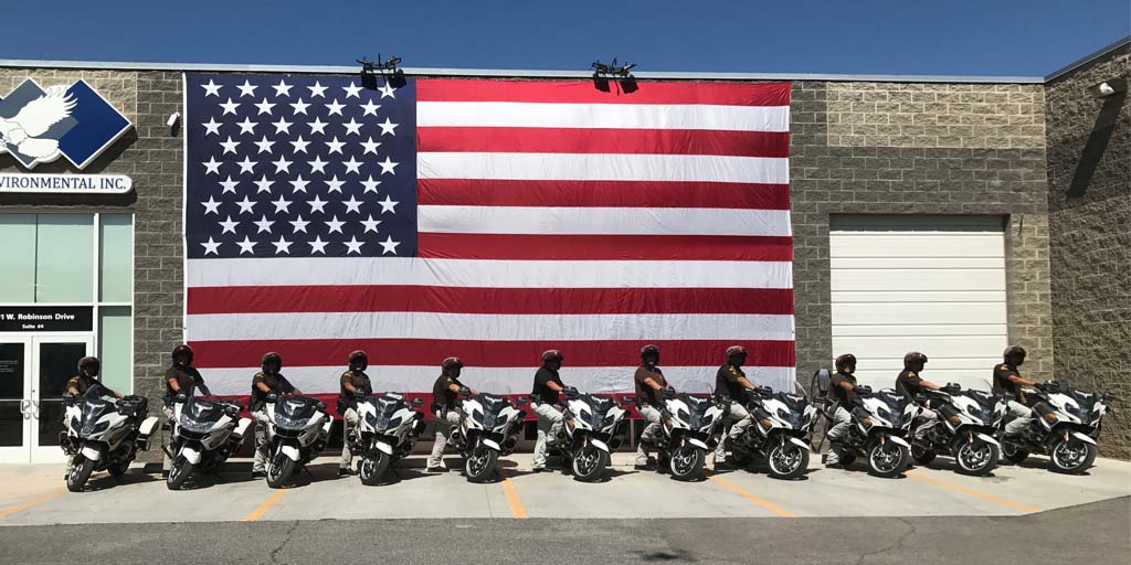 UHP motors line up in front of a large American flag in front of Eagle Environmental