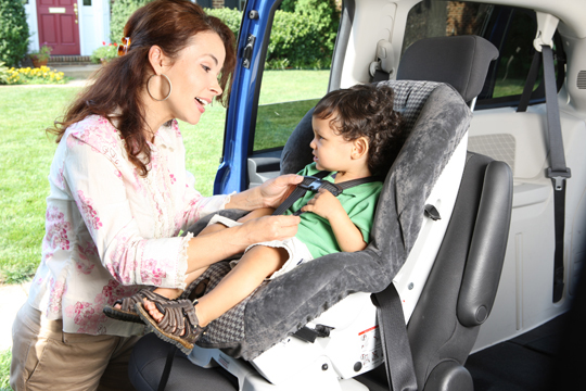 a woman fastens a child into a forward facing car seat