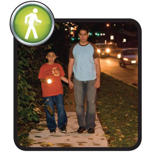 Two people walking on the sidewalk at night with a flashlight