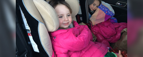 Place jackets and blankets over your children to keep them safely secured in their car seats and warm during the winter.