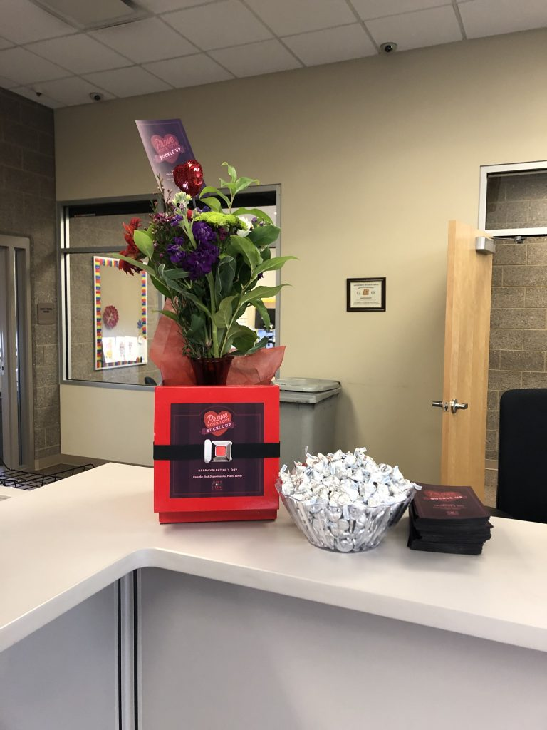 Flower bouquet with bowl of hersheys and a seatbelt reminder card