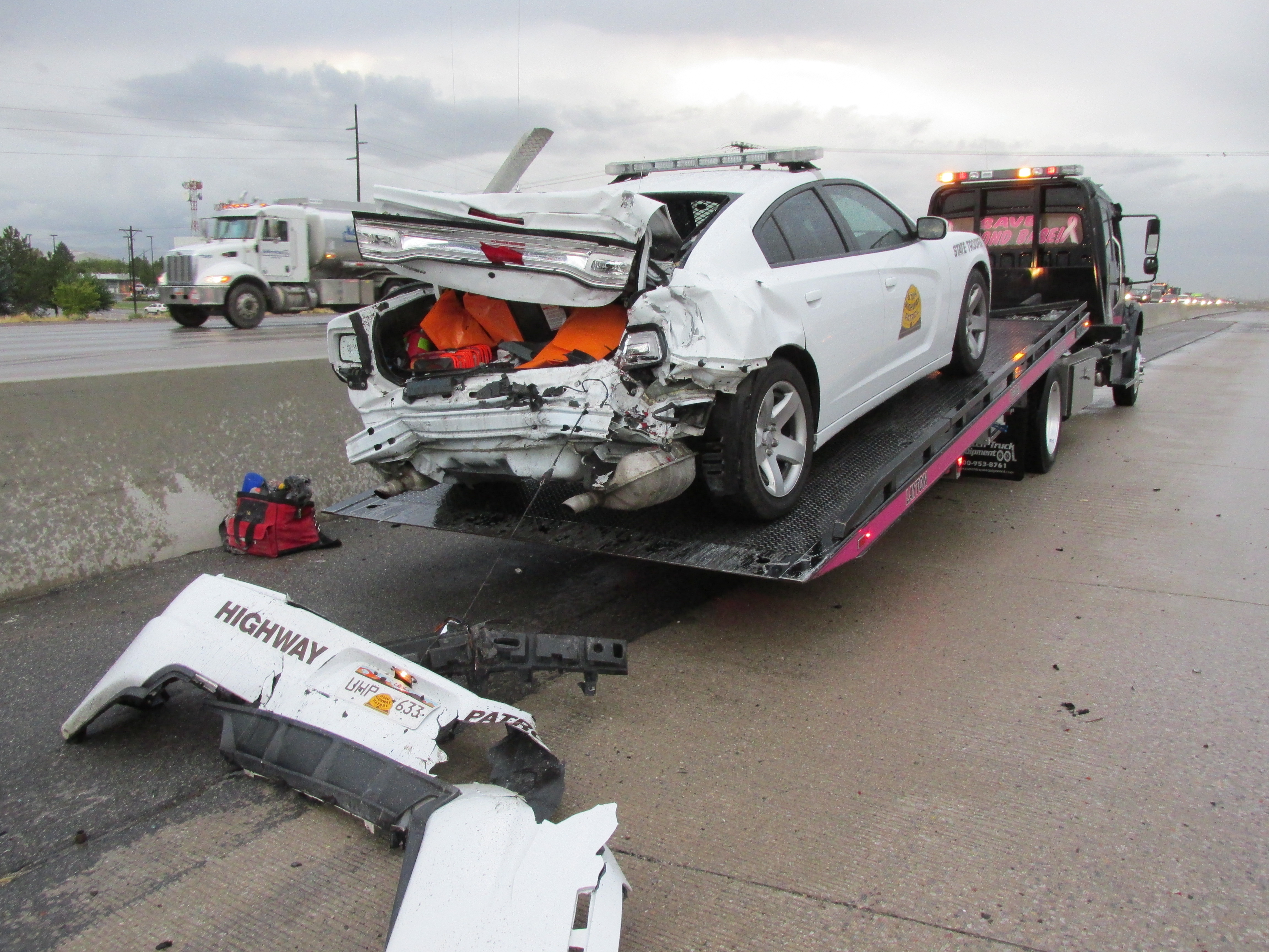 A UHP trooper's vehicle received significant damage when a car crashed into it on the road shoulder.