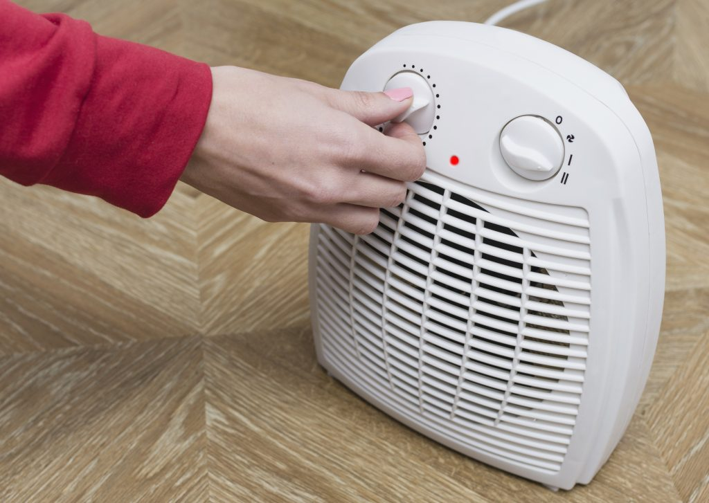 Woman turns on a space heater.