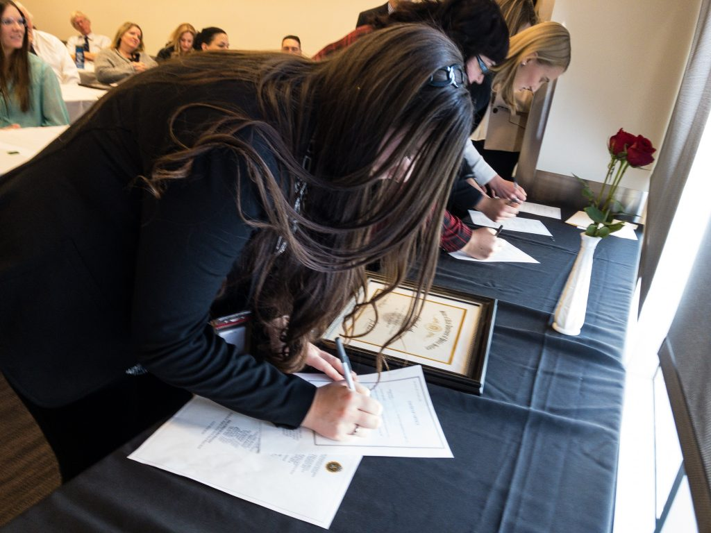 New employees sign their oath of office paper work.