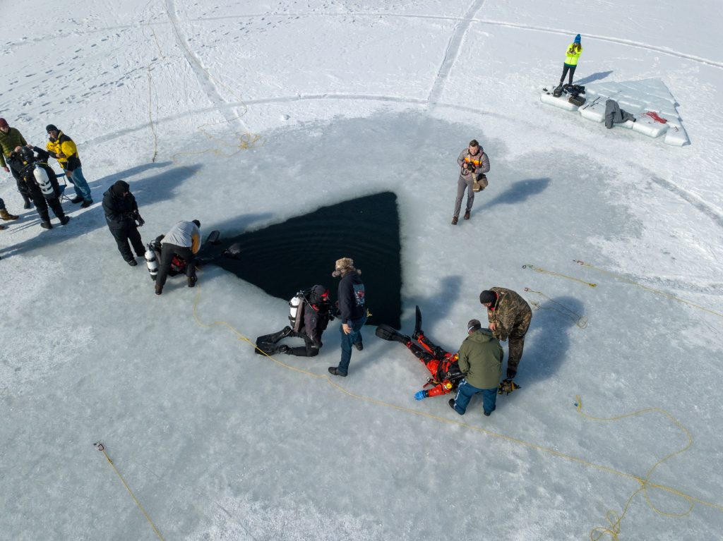 Divers prepare to enter and exit the ice water in this aerial shot.