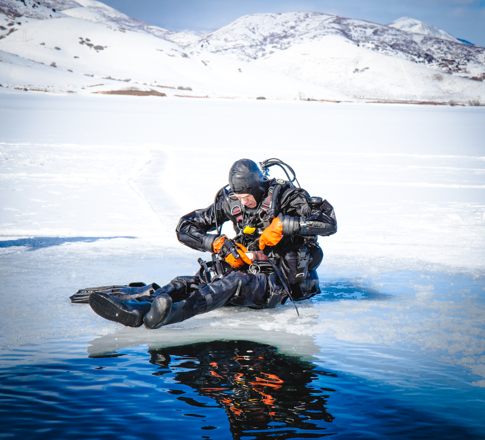 DPS Dive Team member sits at the edge of the hole cut in the ice for ice driving training.