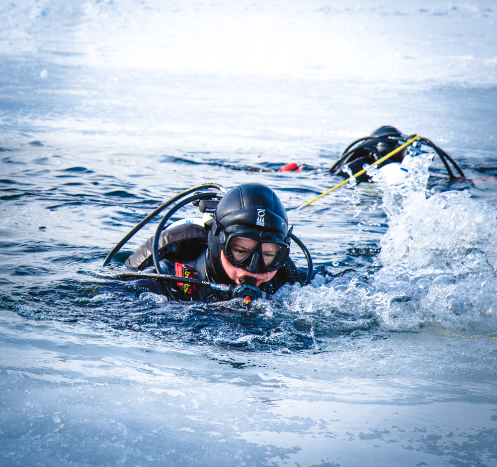 A diver prepares to exit the icy water at ice diving training.
