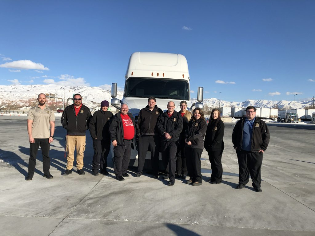 DLD participants in the CDL examiner class pose in front of a semi truck used for training