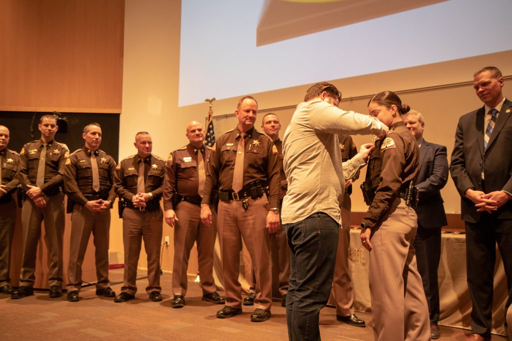 Trooper Vargas has her badge pinned on her by her husband.