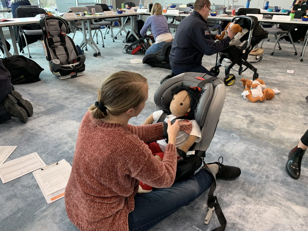 A CPS class students works to properly fit car seat straps around a mannequin.