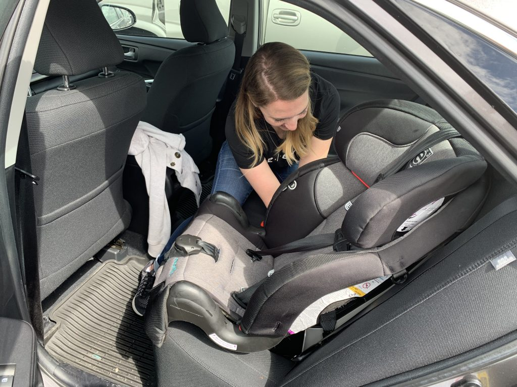 A student in the CPS class works to correctly install a car seat.