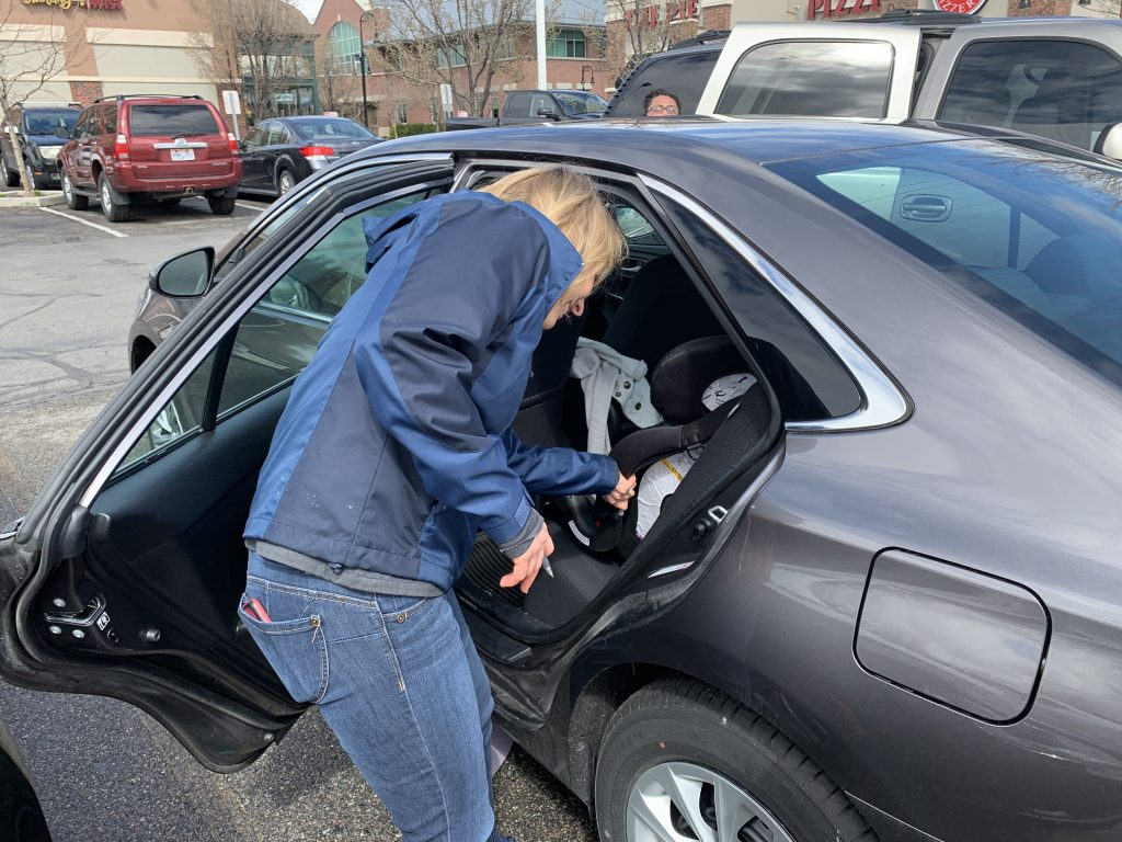 CPS Instructor checking on the installation of a car seat.