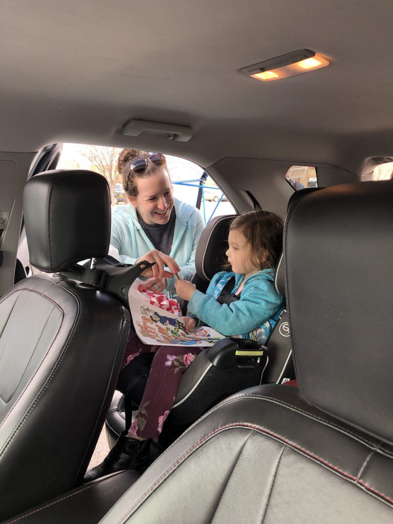 After checking a car seat, a technician gives a child a sticker.