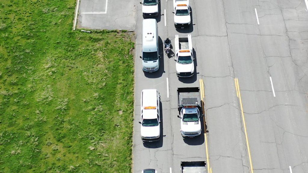 Motorcycle lane filtering between two lanes of stopped traffic.