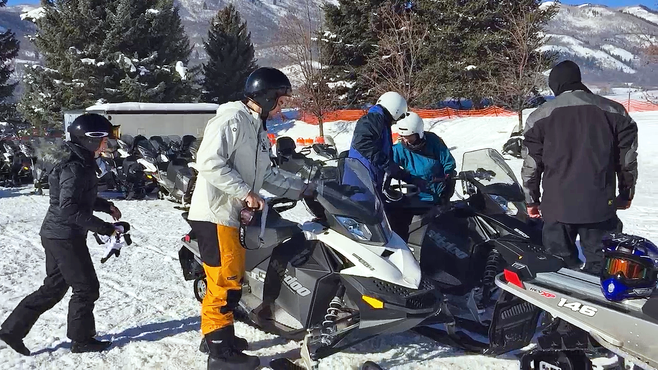 Snowmobilers prepare to head out on a freshly groomed trail